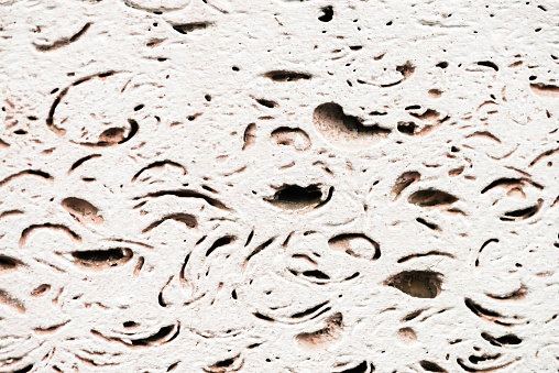 973649382 istock photo Pattern of foam block in macro. Template of foundation of old building. White detailed background from texture of foamed block close-up. Construction from foamed material with copy space. 973649378