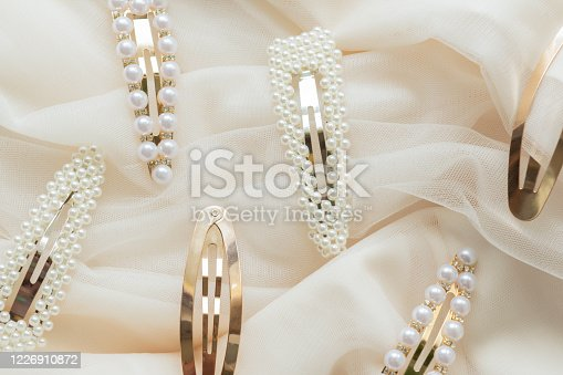 hair accessories trend concept pattern of hair clips with pearls on beige tulle background