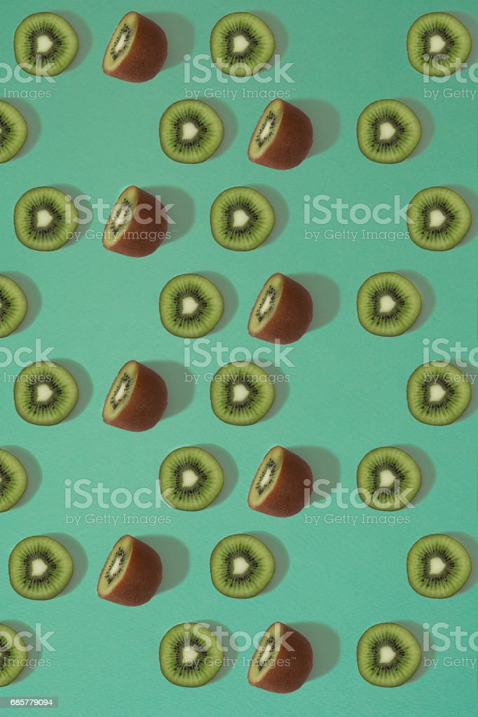 Pattern of kiwi. Top view of the sliced kiwi on blue background. Minimal flat lay concept royalty-free stock photo
