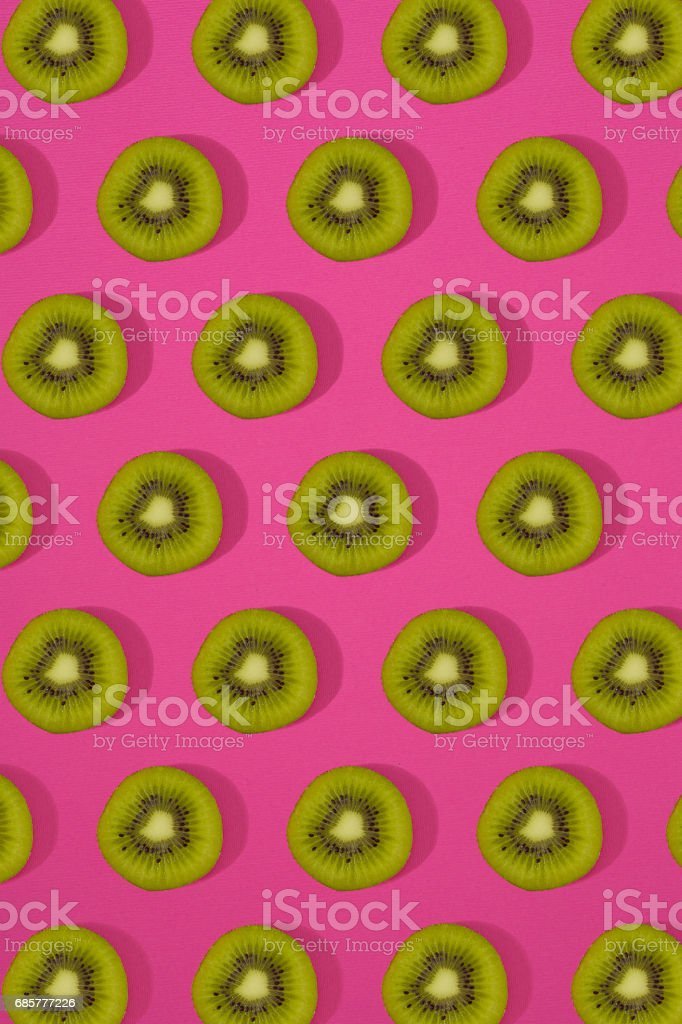 Pattern of kiwi. Top view of the sliced kiwi on pink background. Minimal flat lay concept royalty-free stock photo