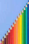 A pattern of multi-colored pencils on a blue background are located diagonally in the image. Stationery for school and kindergarten. Products for drawing and fine art.