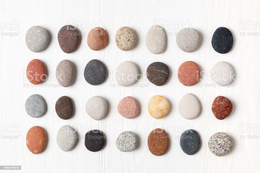 Muster der natürlichen bunten Kieselsteinen auf weißem Hintergrund aus Holz. – Foto
