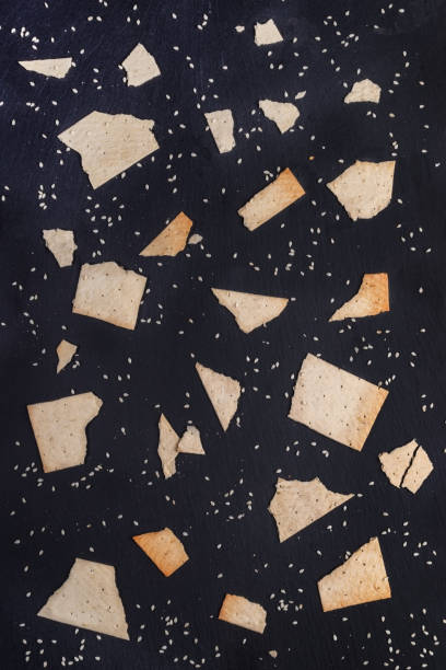 Pattern of pieces of wheat crispbreads with sesame seeds on dark grey shale background. Pattern of randomly broken down pieces of wheat crispbreads of different sizes with white sesame seeds on dark grey shale board background. Healthy snaks. Top view, flat lay. arbitrary stock pictures, royalty-free photos & images