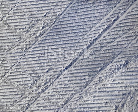 A pattern of relief footprints in the snow after cleaning the ski slope with a snowcat. Grunge knurled snow background with ski slope