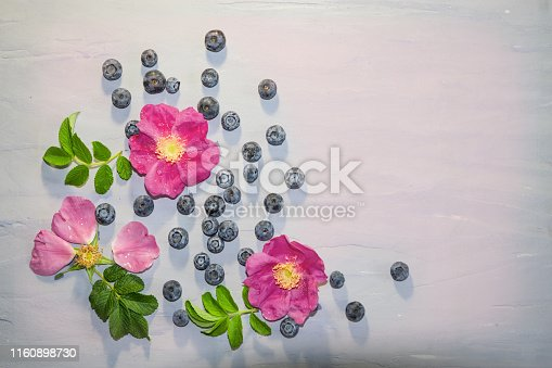 867774250istockphoto A pattern of rose hip flowers with green leaves and blueberries on a light gray cement background, 1160898730