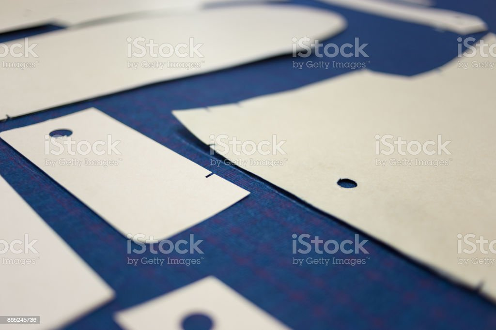 Pattern pieces for a bespoke suit arranged on fabric. stock photo