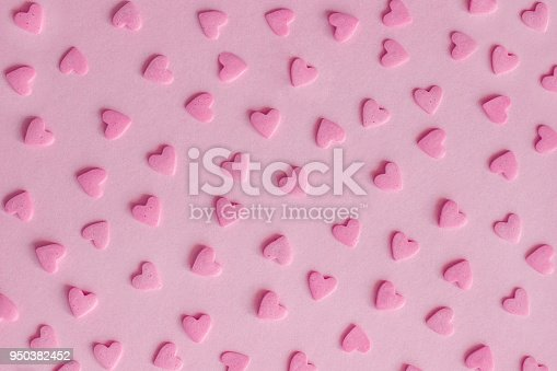 istock Pattern. Pink confectionery hearts on pink background, texture 950382452