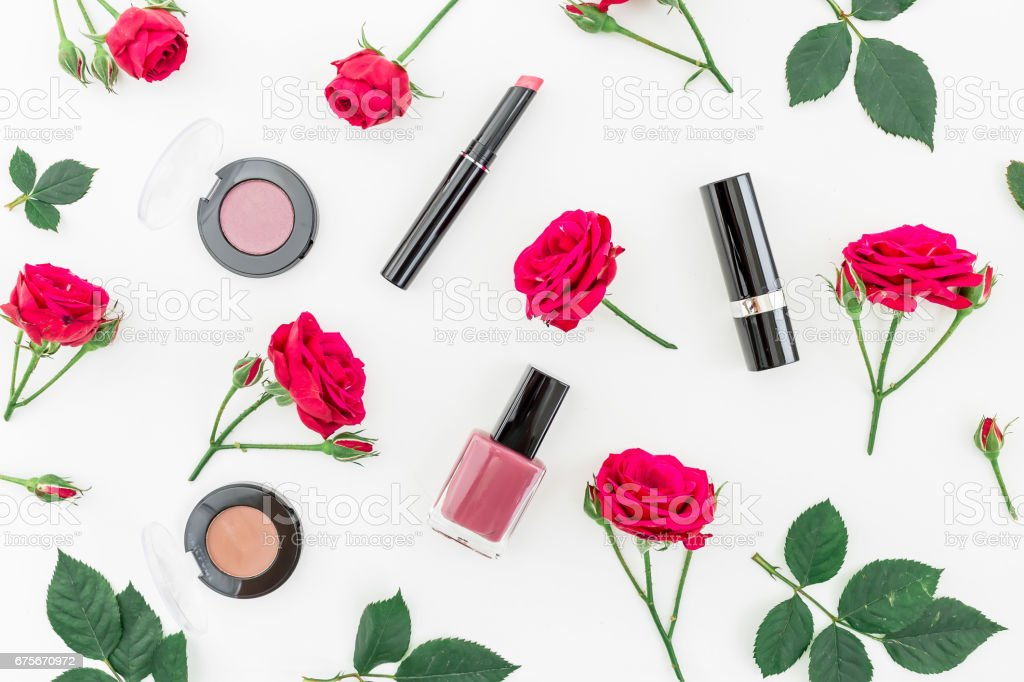 Pattern with red roses and woman cosmetics on white background. Flat lay, top view. Beauty background royalty-free stock photo