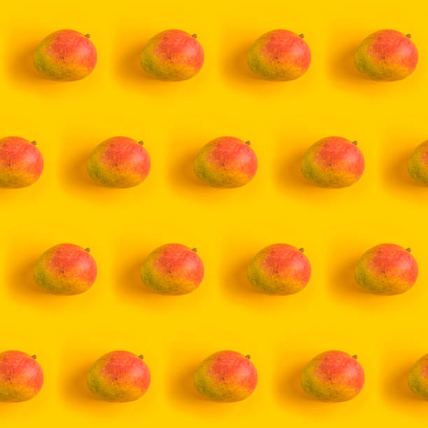 Pattern with ripe mango on yellow background. Top View. Copy Space. Pop art design, creative summer concept. Mango in minimal flat lay style. stock photo