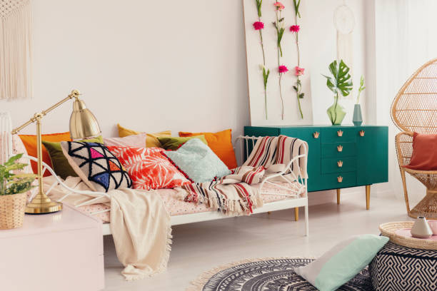 patterned and colorful pillows on single metal bed in stylish girl's bedroom interior with peacock chair and green cabinet with crown shape handles - home decor boho imagens e fotografias de stock