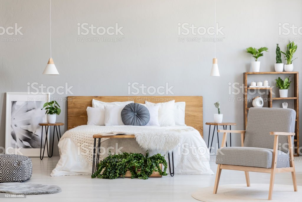 Patterned armchair and plants in bright bedroom interior with poster next to wooden bed. Real photo