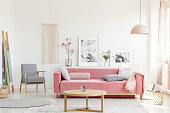 Patterned armchair next to pink sofa in apartment interior with posters and wooden table. Real photo