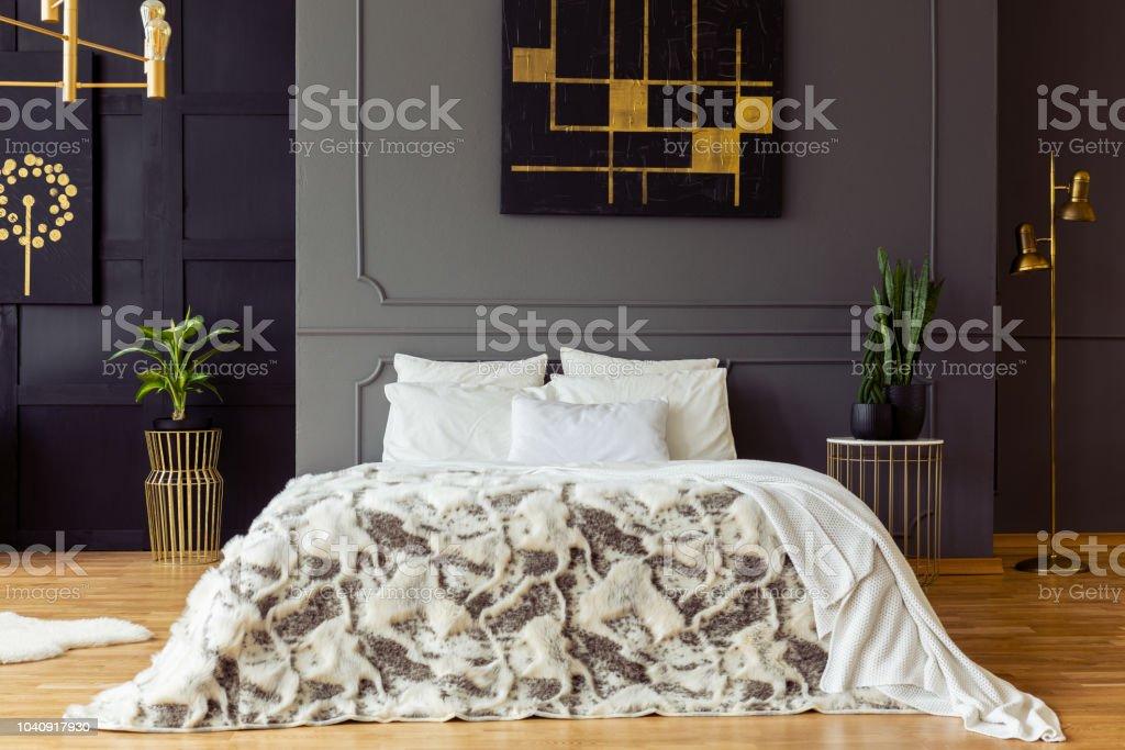 Gemusterte Bett Gegen Graue Wand Mit Schwarzgoldenen Poster ...