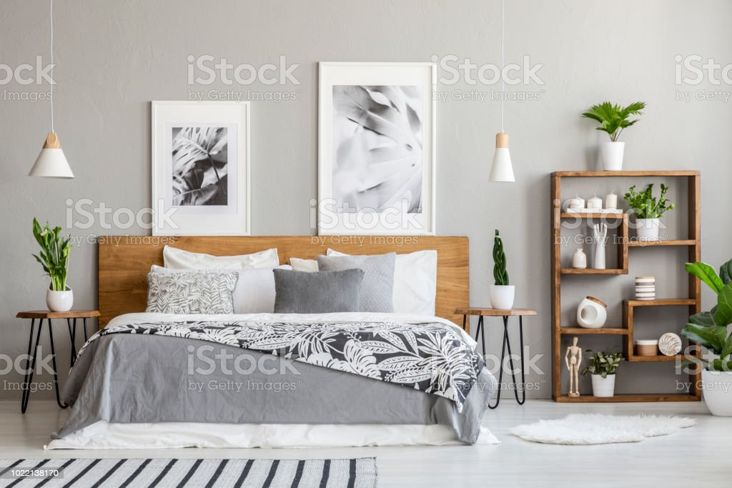 Gedessineerde deken op houten bed tussen tabellen met planten in