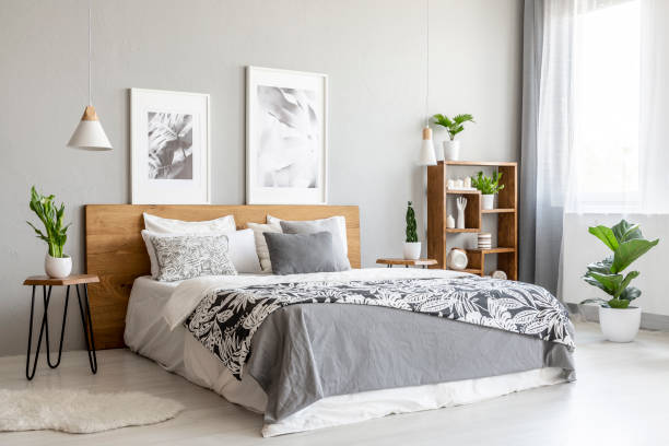 Patterned blanket on wooden bed in grey bedroom interior with plants and posters. Real photo stock photo