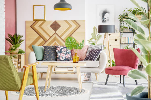 Patterned cozy living room Patterned pillows on sofa next to red armchair in cozy living room interior with wooden furniture cushion stock pictures, royalty-free photos & images
