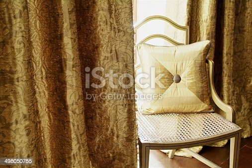 Closeup of neutral cushion on chair by curtains in daylight