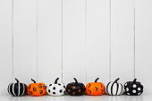 istock Patterned Halloween pumpkins in a row against a white wood background 1174282750