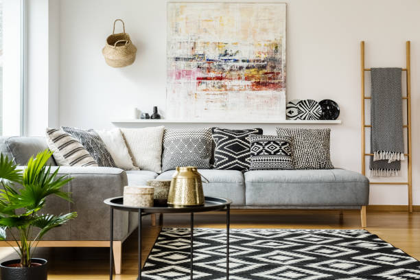 patterned pillows on grey corner sofa in living room interior with table and painting. real photo - home decor boho imagens e fotografias de stock