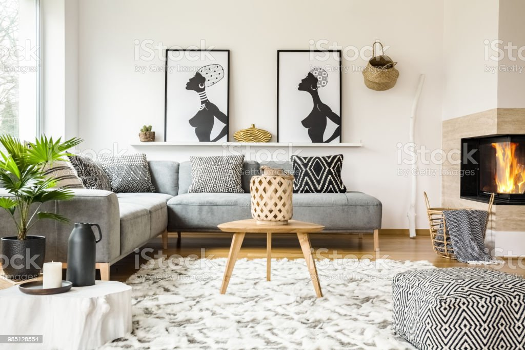 Patterned pouf next to wooden table in african living room interior...