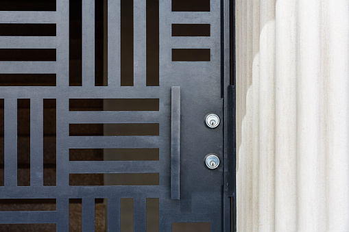Patterned screen security door, black color with horizontal cut outs. intentional composition with diffused light