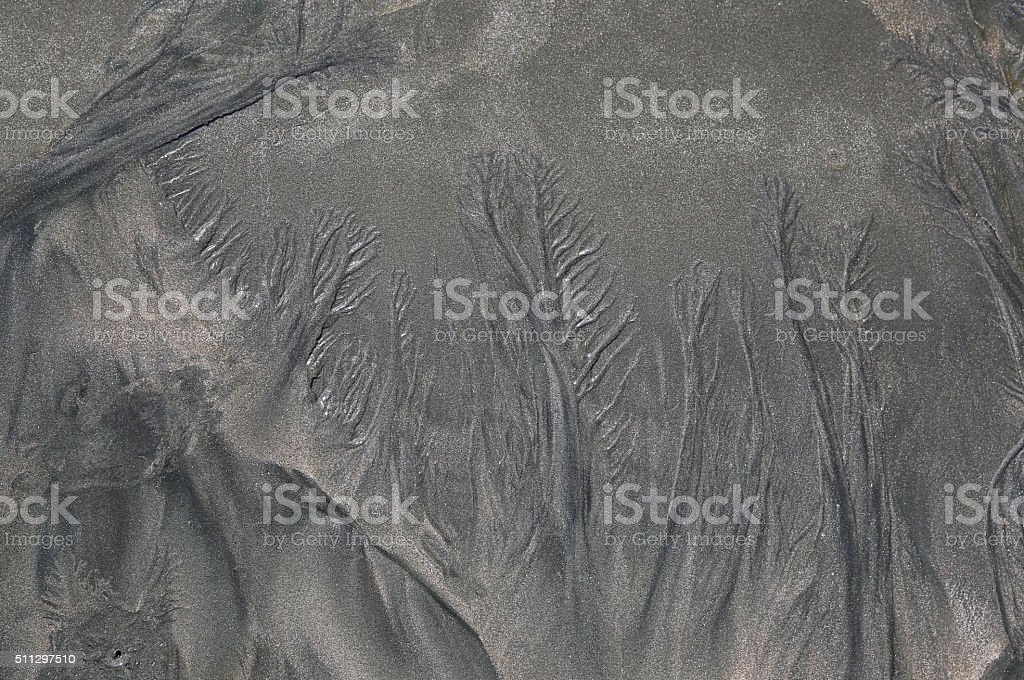 Patterns In Black Sand Caused By Waves stock photo