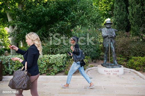 Aix-en-Provence, France - May 30, 2014: Two women holding smartphones walk past a statue of Paul Cézanne (1839–1906), a French artist and Post-Impressionist painter, in Aix-en-Provence, France