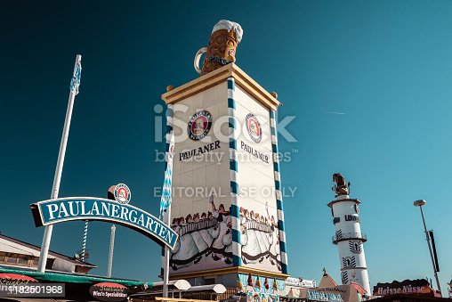 Munich, Germany - October 1, 2019: Paulaner Beer Garden during Oktoberfest in Munich with its famous symbol and the Löwenbräu lion in the background