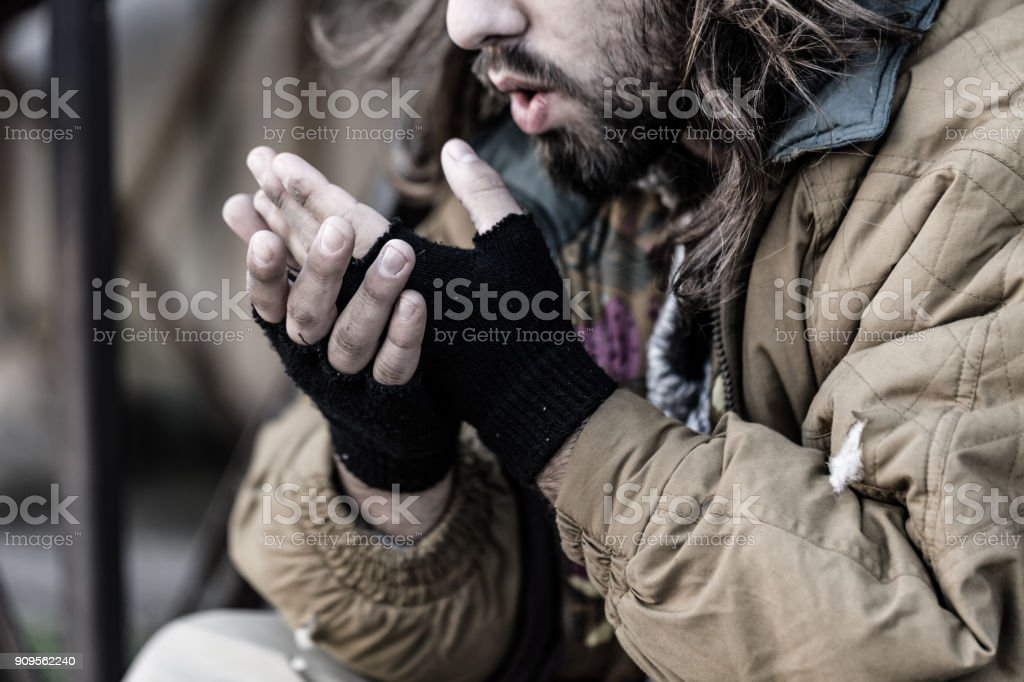 Pauper blowing on cold hands stock photo