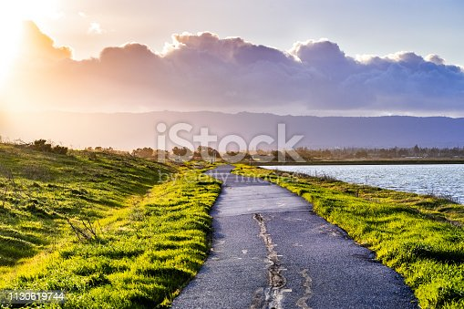 Paved trail illuminated by the evening sunlight on the shoreline of south San Francisco bay area, Mountain View, California