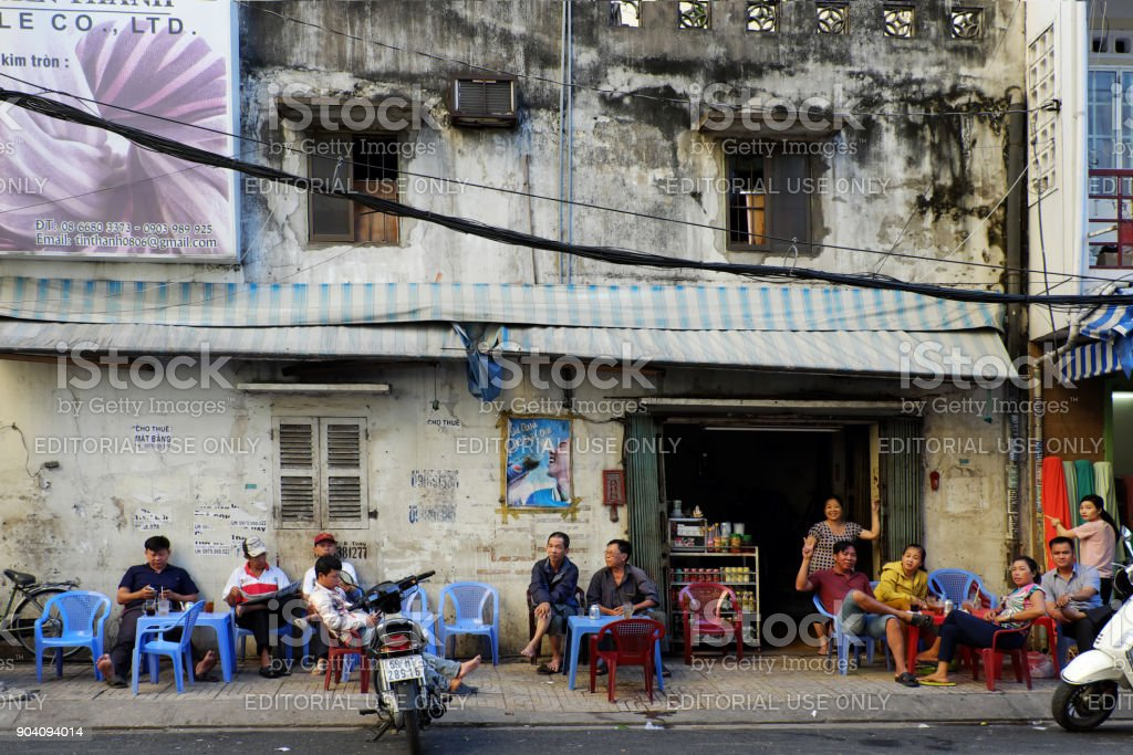 pavement coffee shop HO CHI MINH CITY, VIET NAM- NOV 21, 2017: Group of Asian people sit at pavement coffee shop at morning, sidewalk cafeteria is Vietnamese cultural where people can chat together, Vietnam Adult Stock Photo