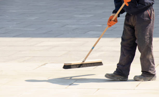 Pavement construction worker filling the block joints with sand using long broom