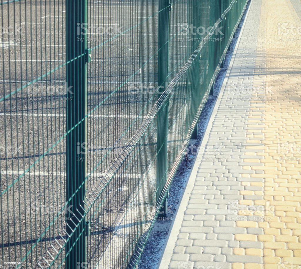 Pavement of pavement along the green fence mesh foto stock royalty-free