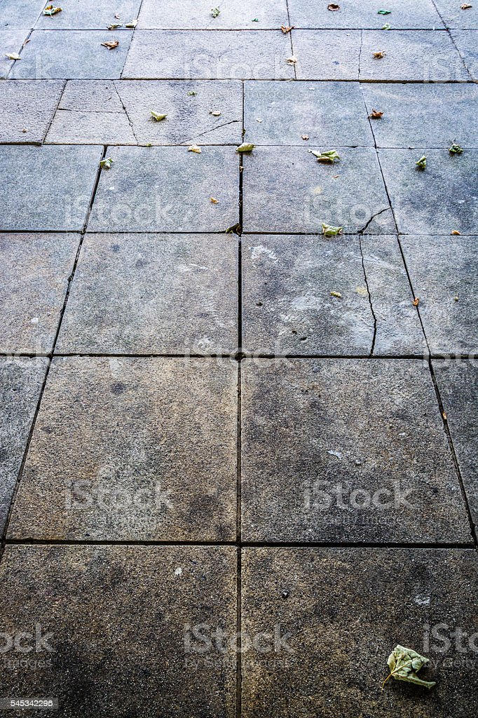 Pavement texture with fallen leaves - abstract background vertical stock photo