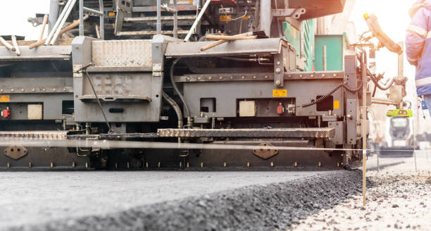 Paver machine is laying fresh asphalt on city road