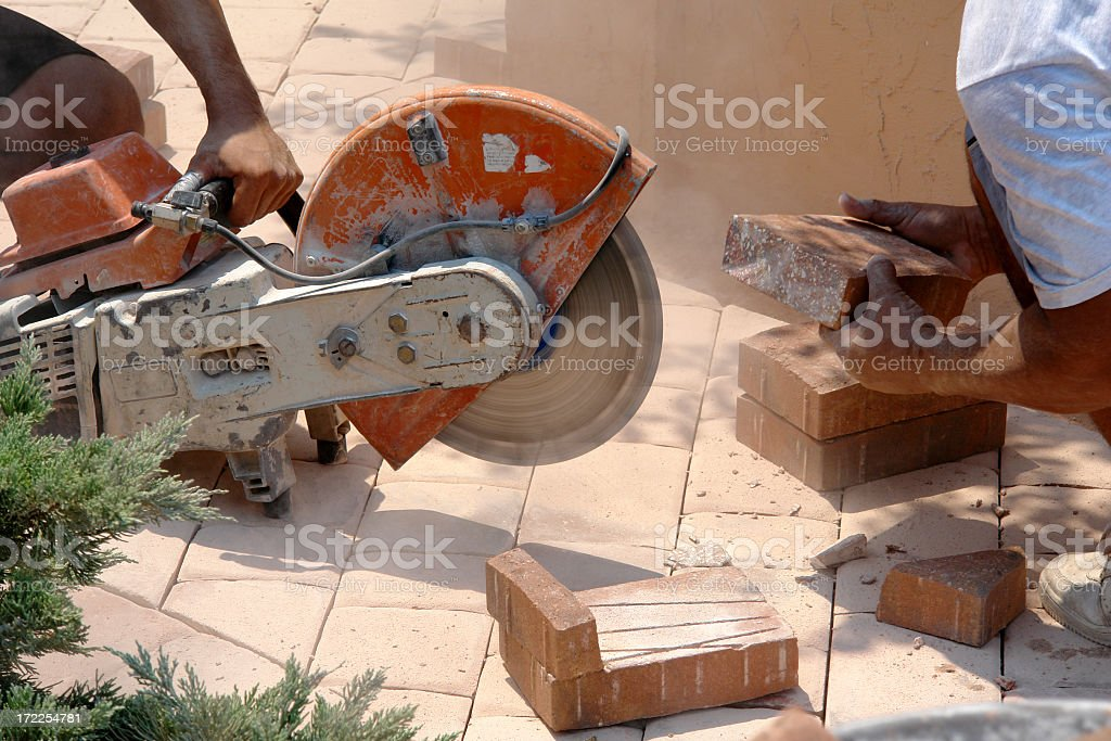Paver worker cross cuts a stone stock photo