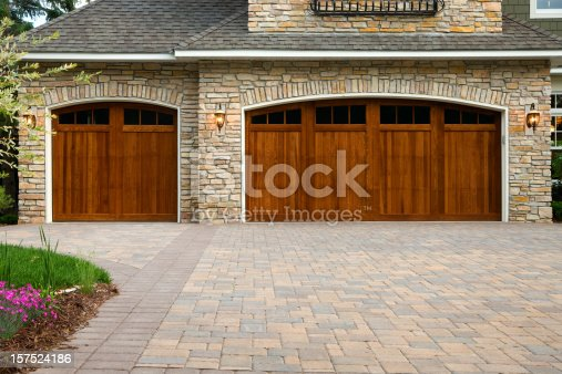Pavers, wood custom garage doors, landscaping and beautiful stone exterior walls on a custom home.