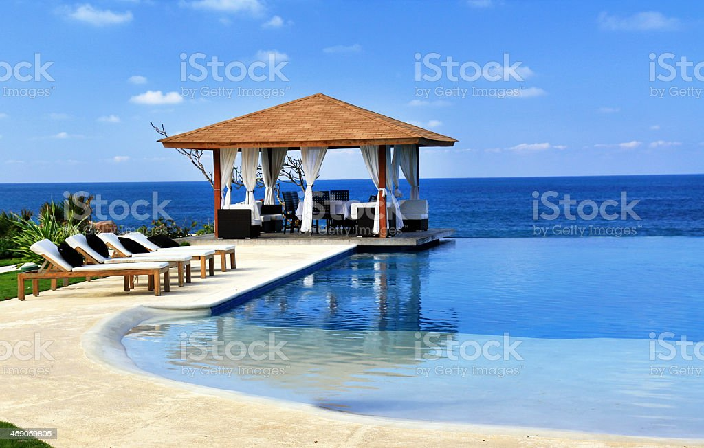 Pavilion and sun lounges next to a resort swimming pool stock photo