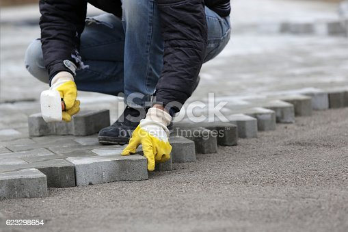 Paving stone worker is putting down pavers during a construction of a city street.