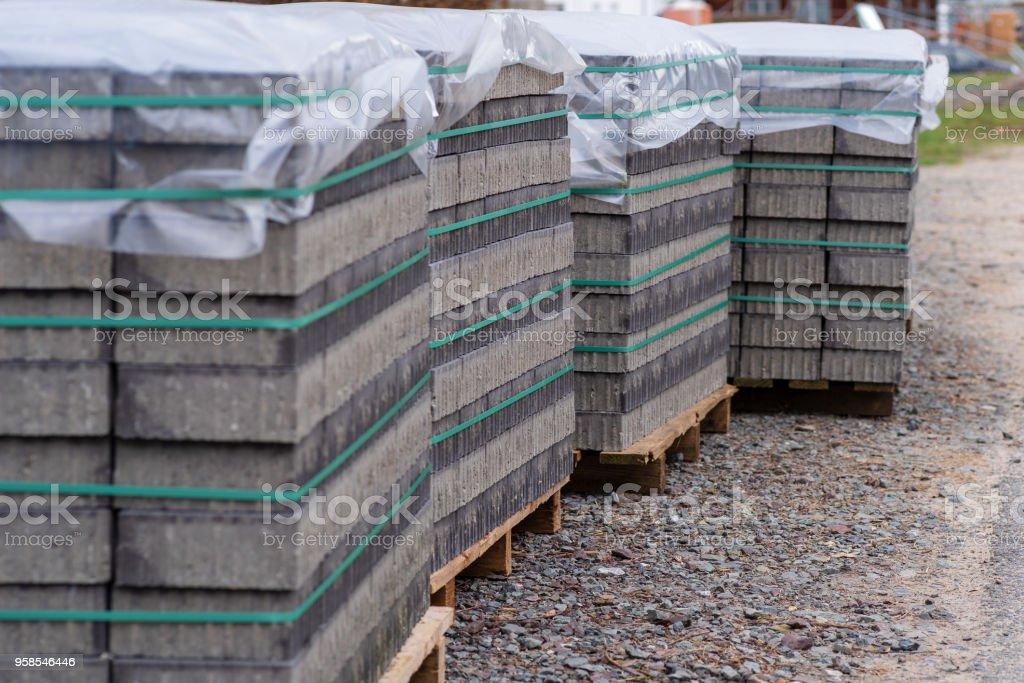 Pflastersteine auf mehreren Paletten als Regenschutz mit Folie abgedeckt. – Foto