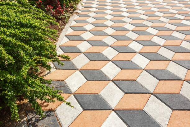 paving the yard with colored paving tiles in the shape of a diamond. - zona pedonale struttura creata dall'uomo foto e immagini stock