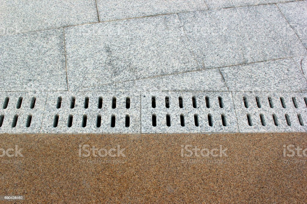 Paving tiles on a sidewalk with underground water drainage culvert stock photo