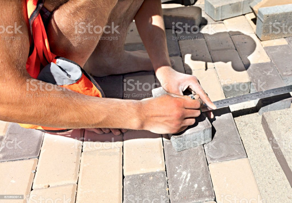 Paving tiles on a terrace with a ruler and measuring stock photo