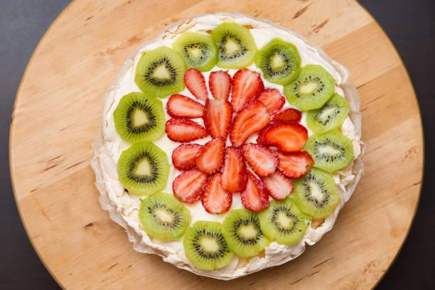 Pavlova Cake Traditional Iconic Australian Dessert. Homemade Meringue Pie Decorated with Fresh Fruit Strawberry and Kiwi stock photo