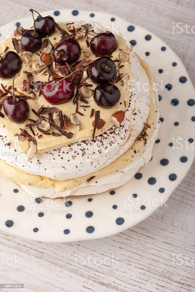 Pavlova-Kuchen mit frischen Kirschen auf dem Keramik-Platte vertikal Lizenzfreies stock-foto