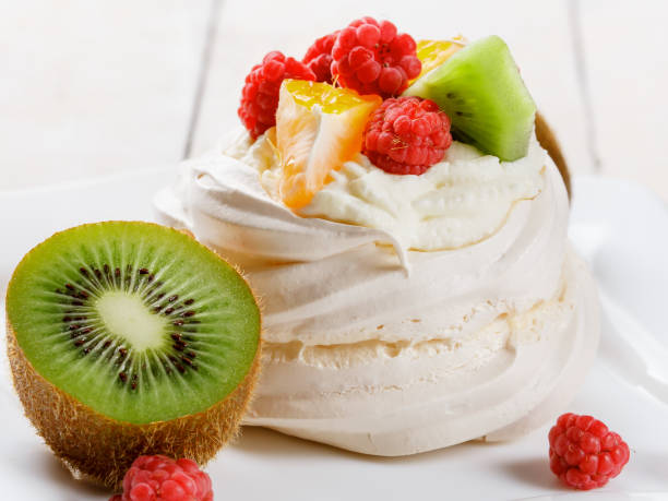 Pavlova sweet cream dessert with berries and fruits on white wooden background. Delicious food. stock photo