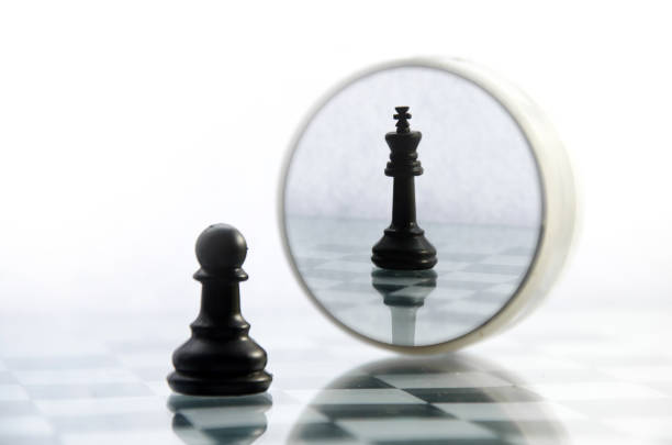 pawn pieces on the chessboard, the reflection in the mirror king stock photo