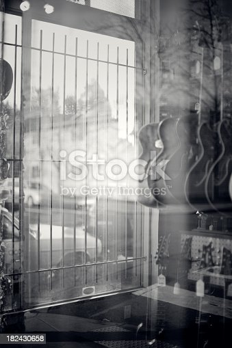 Electric guitars are visible hanging through a store front window, the glass clouded by reflections of the trees behind.  Vertical with copy space.