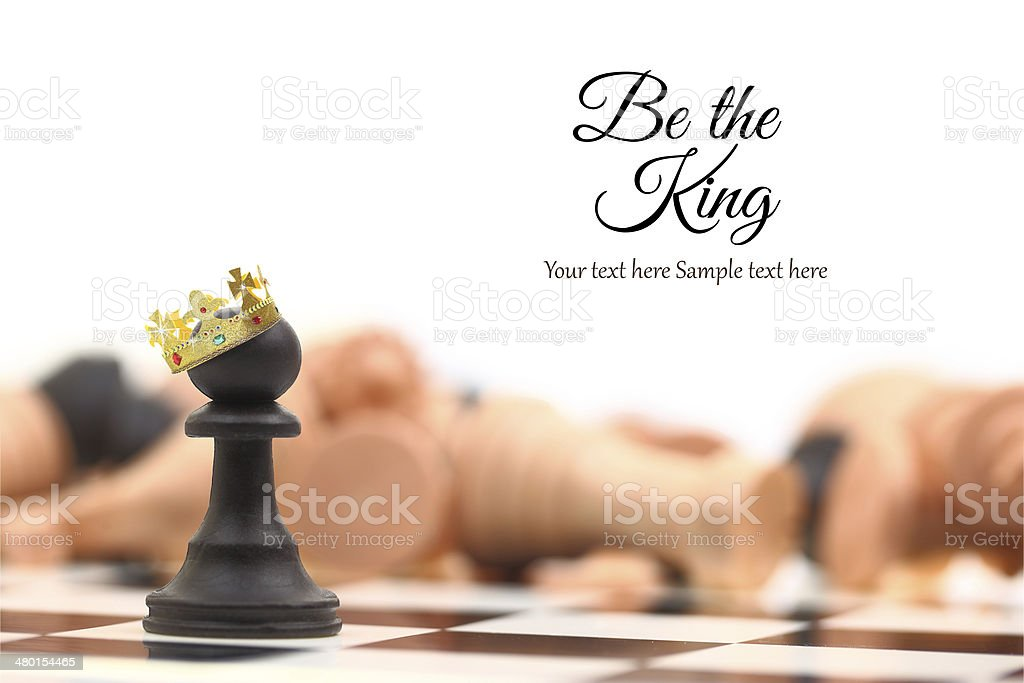 Pawn winner standing crowned as king with copy-space royalty-free stock photo