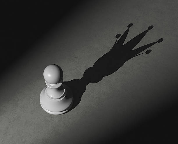 Pawn with shadow of the king stock photo